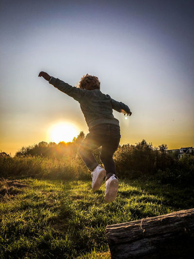 Woman jumping on field against sky during sunset