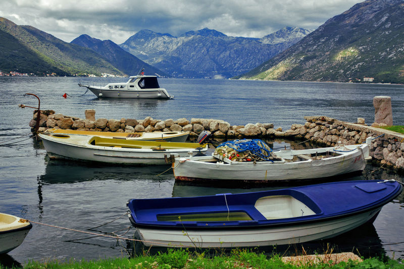 Boats moored in lake against mountains