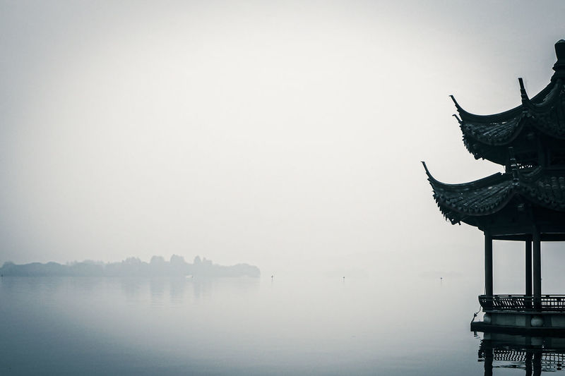 Cropped image of traditional gazebos on lake during foggy weather