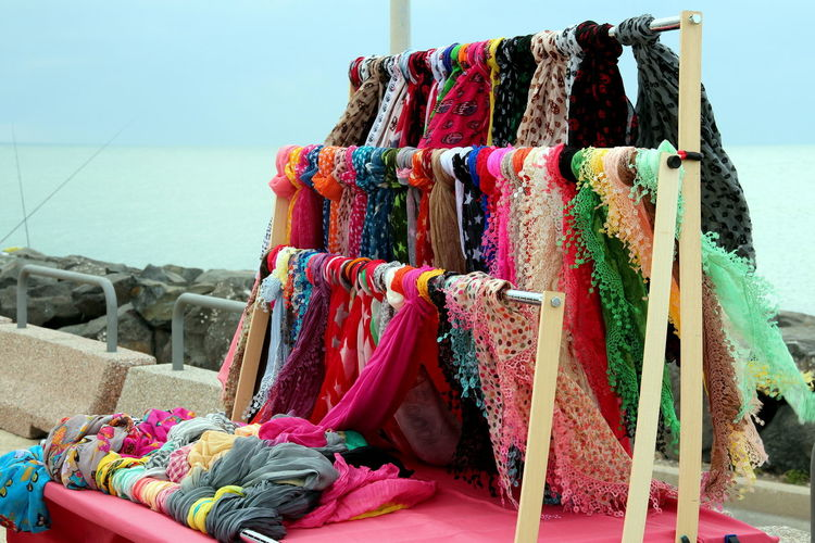 Stand with colorful scarves blowing in the wind, on the pier EyeEm Best Shots EyeEm Selects Abundance Choice Clothing Day Focus On Foreground For Sale Hanging In A Row Market Multi Colored Nature No People Outdoors Retail  Retail Display Sale Scarf Scarves Sea Stall Textile Variation Water