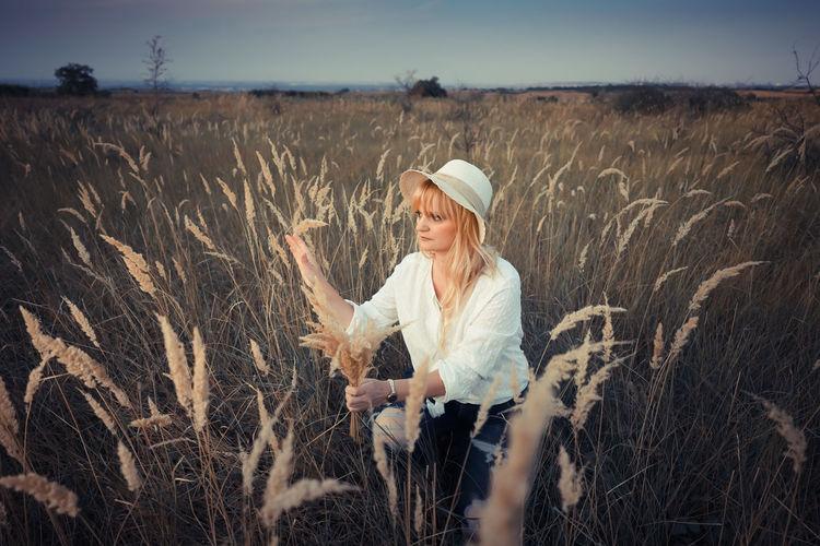 Woman wearing hat sitting in field