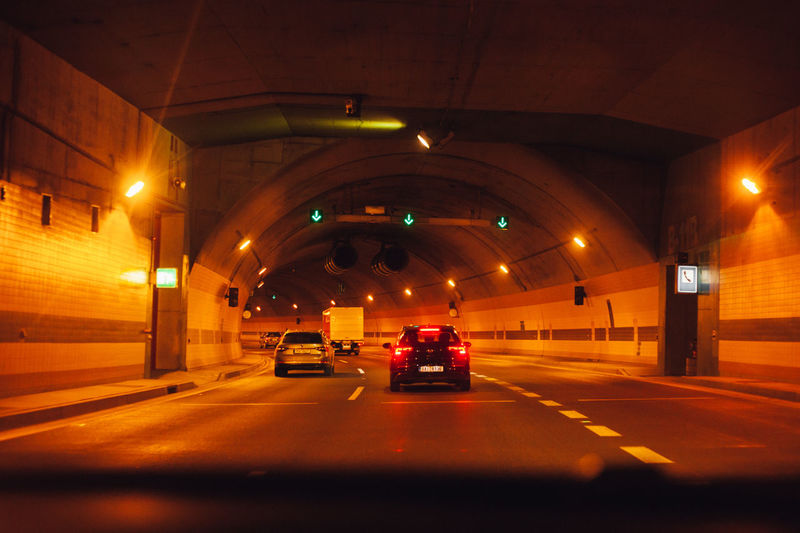 Cars on road in illuminated tunnel