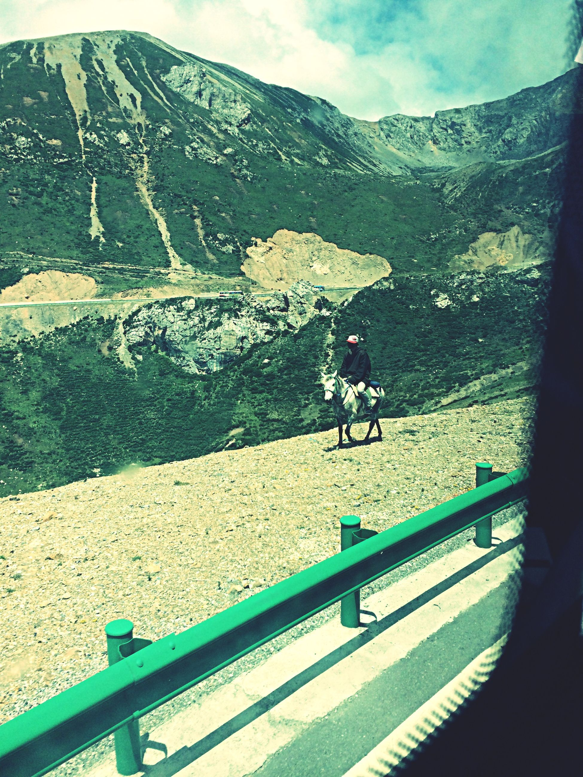mountain, transportation, sky, railing, road, mountain range, men, nature, mode of transport, lifestyles, high angle view, leisure activity, scenics, beauty in nature, water, travel, tranquility, day, unrecognizable person