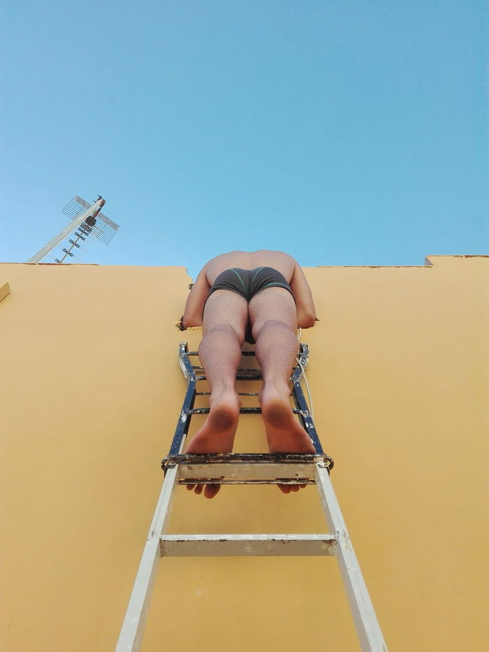 Low section of shirtless man on ladder against clear sky