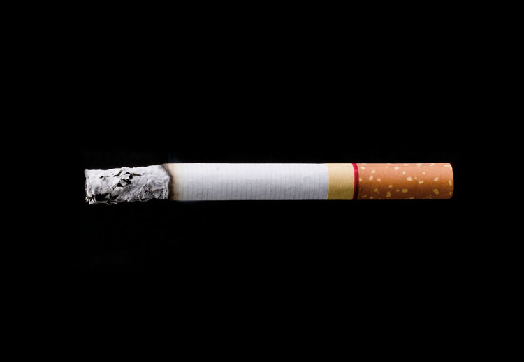 Close-up of cigarette over black background