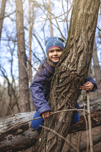 Portrait of boy on tree trunk during winter