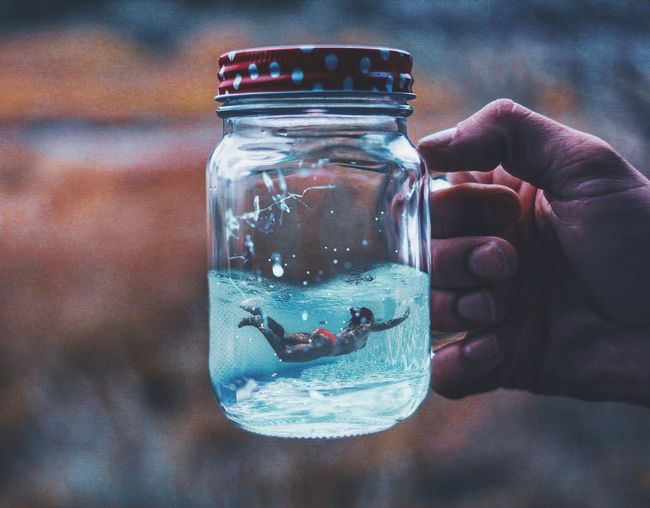 Cropped Hand With Woman Swimming In Jar