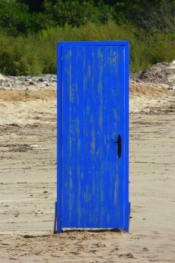 Absence Beach Blue Container Day Door Environment Field Land Metal Nature No People Outdoors Plant Plastic Safety Sand Single Object Tree Wall - Building Feature Wood - Material