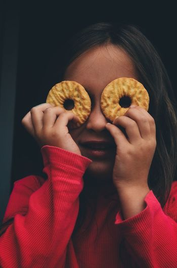 Portrait of girl holding cookies in front of eyes