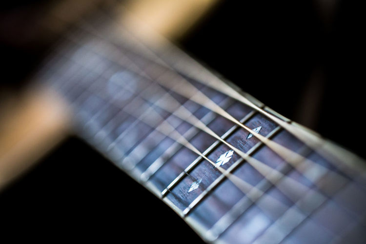 Close-up of guitar fretboard over black background