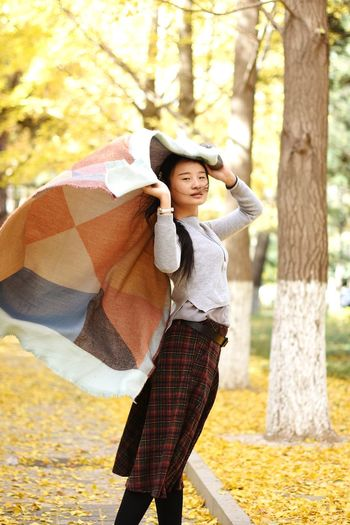 Portrait of young woman standing in park during autumn