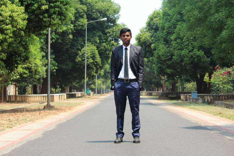 Full length portrait of young man wearing suit standing on road against trees