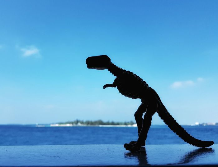 Toy dinosaur silhouette on blue sky and sea