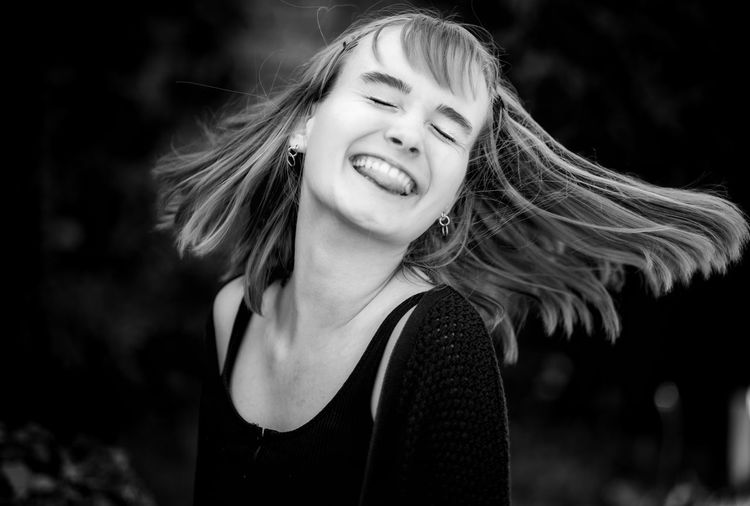 Close-up of smiling teenage girl tossing hair