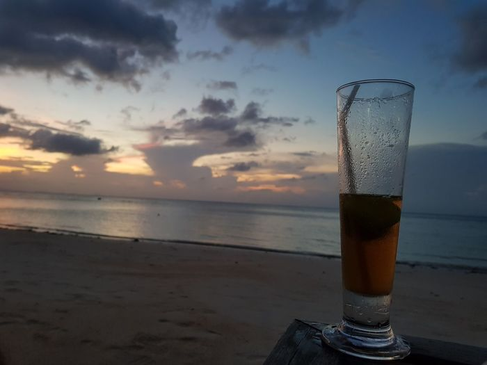Glass of beer on beach against sky during sunset