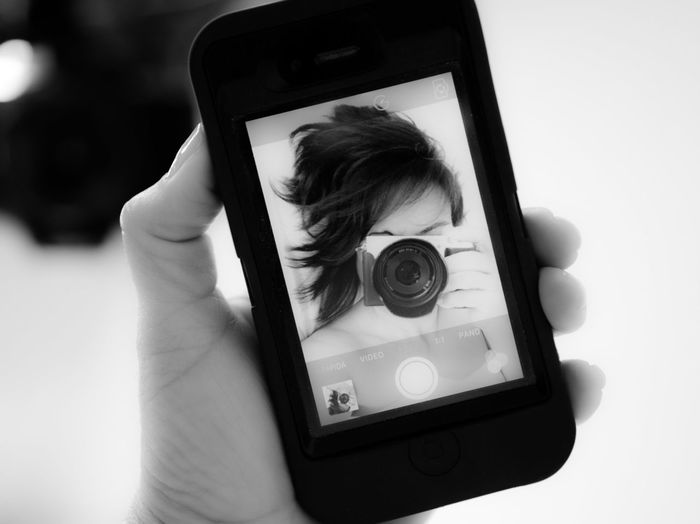 Close-Up Of Mobile Phone With Photograph Of Woman Holding Camera