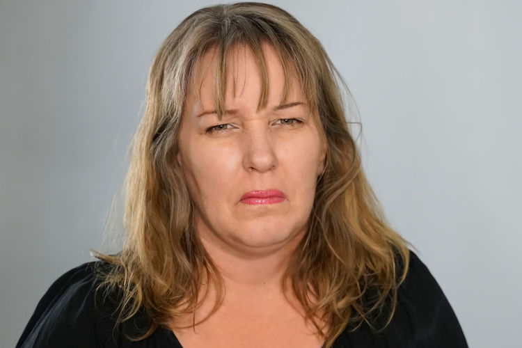 Portrait of woman making a face against gray background