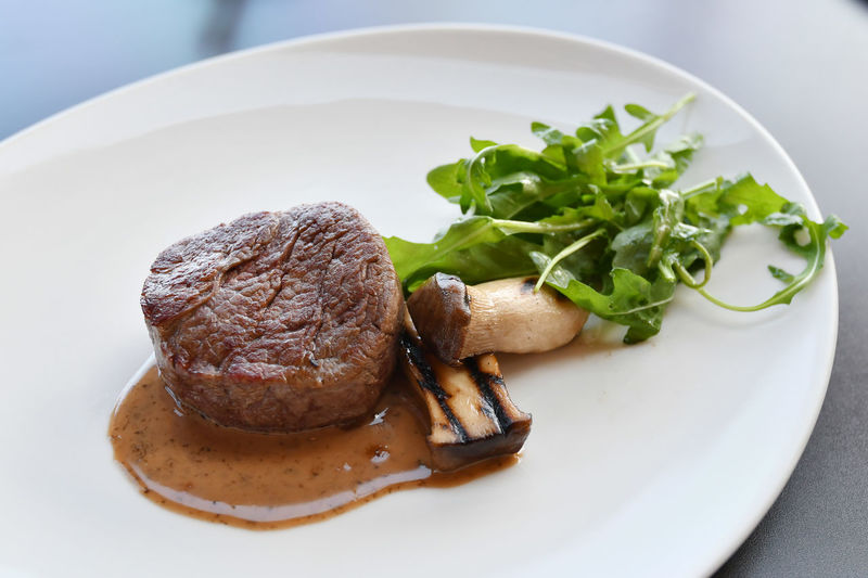 High angle view of steak with mushroom and herbs served on table
