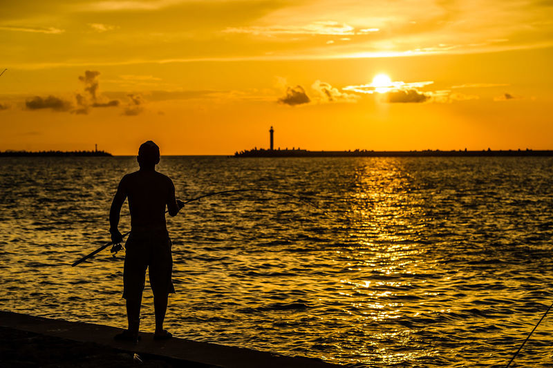 Silhouette man fishing at sea shore against sky during sunset