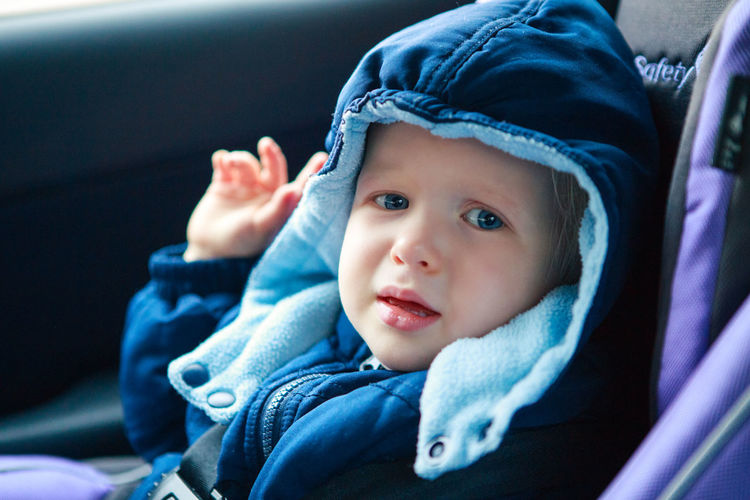 Crying sad caucasian baby infant sitting in car seat. kid in outwear clothes in automobile  carsit