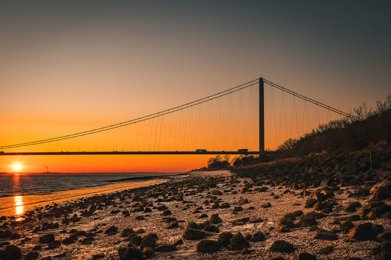 View of suspension bridge at beach during sunset
