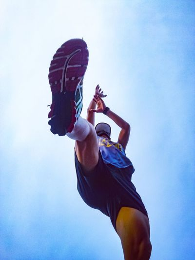 Low angle view of man playing basketball against sky