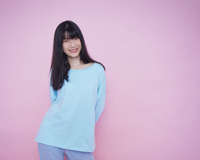 Portrait of smiling young woman standing against pink background