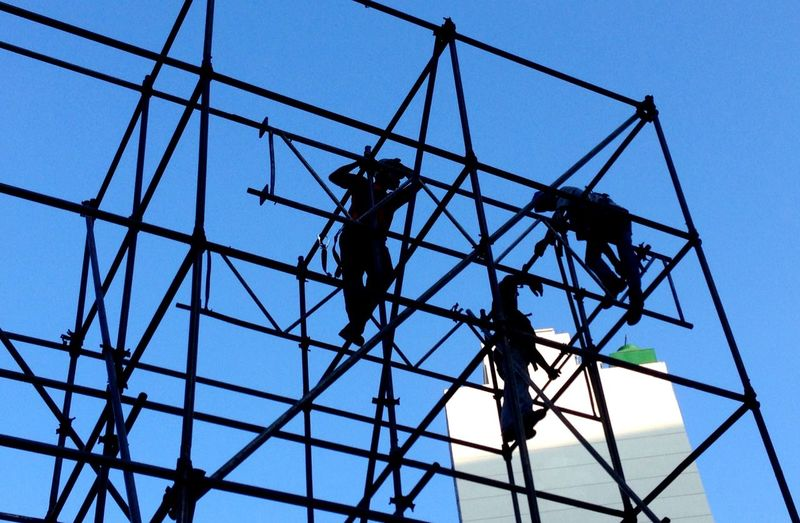 Low angle view of silhouette manual workers on scaffoldings against clear sky