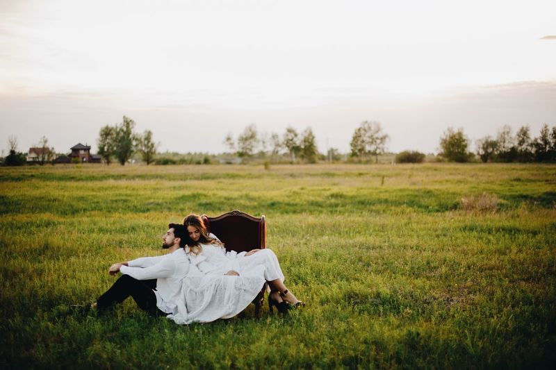 Bride and groom on field against sky