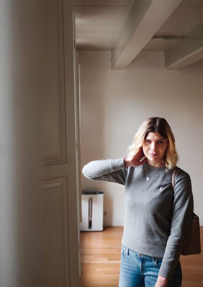 Portrait of woman standing against door at home