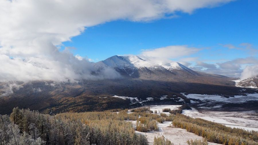 Scenic View Of Mountains At Xinjiang Kanas National Geopark Against Cloudy Sky