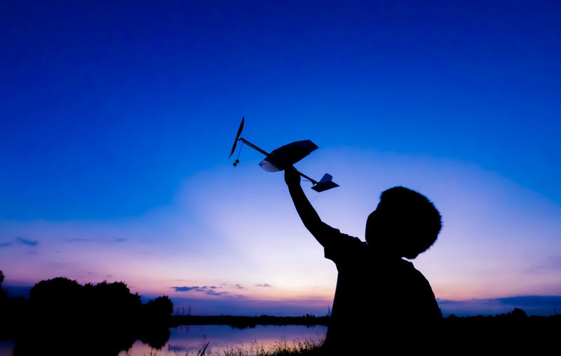 Silhouette of boy playing with toy airplane against sky