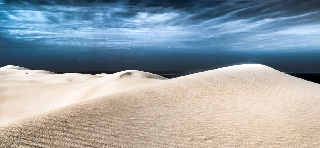 Scenic view of sand dunes at desert against cloudy sky
