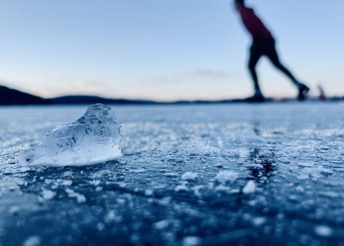 Low section of person on frozen sea against sky