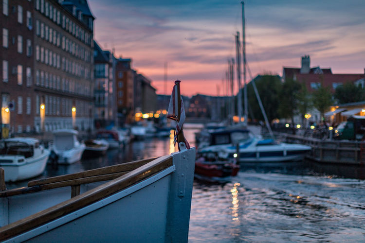 Sailboats moored on river in city at sunset