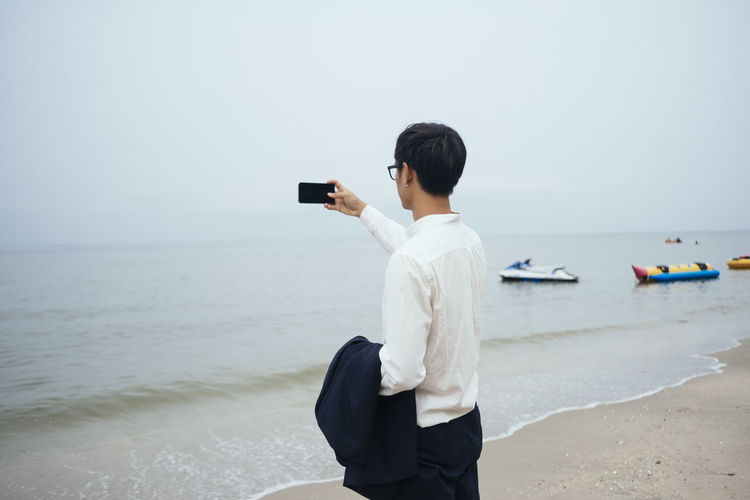 Man using mobile phone at beach against sky