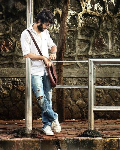 Whites and denim blues never go out of trend. Cityslicker Candid Portrait Beard Glasses Street Photography Streetstyle Fashion Dailywear UrbanTrends Denim Rippedjeans  Whiteshirt  Messengerbag Leatherbag Busstop Crome  Mumbai India