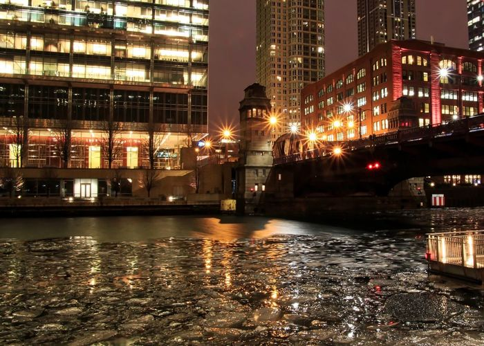City lights illuminate with light beams are reflected in icy Chicago River on winter evening . Evening City Night Lights Bridgehouse Drawbridge  Frozen River Commuting Pedestrian Walkway Light Beams Chicago Chicago River Chicago El Chicago Loop Downtown Chicago Elevated Track Ice Winter Architecture Building Exterior Built Structure City Elevated Train Frozen River Icy Illuminated Night No People Outdoors Reflection Sky Water