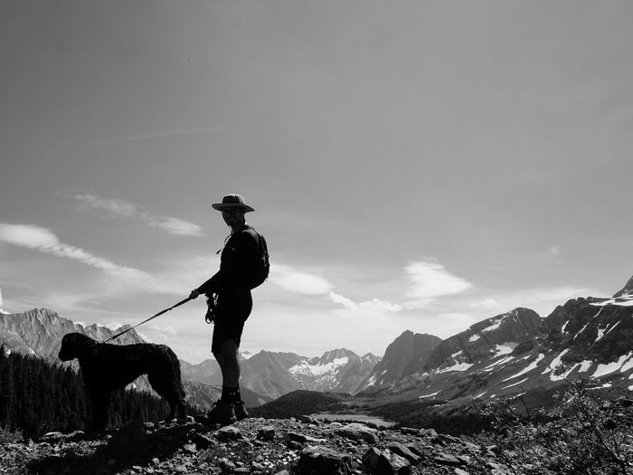 Man standing on mountain against sky with dog