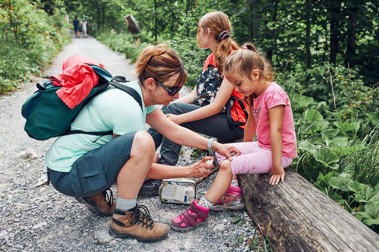 Mother dressing the wound on her little daughter's knee with medicine in spray. accident during trip