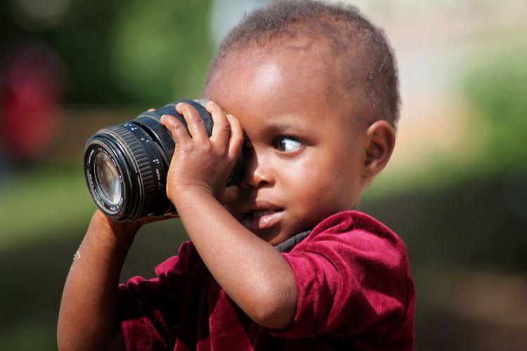 Close-Up Of Boy Looking Through Camera Lens