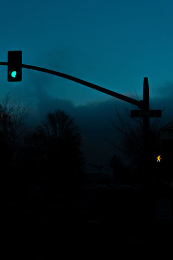 Low angle view of road signal against clear sky at dusk