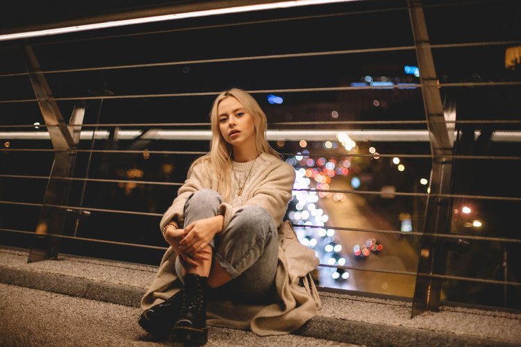 Portrait of young woman sitting on railing