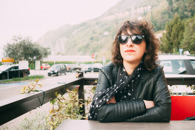 Confident woman wearing sunglasses and jacket while sitting at outdoor cafe