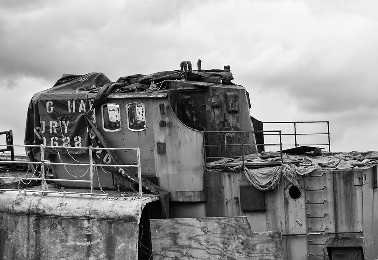 LOW ANGLE VIEW OF OLD ABANDONED SHIP AGAINST CLOUDY SKY