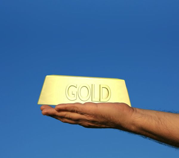 Close-up of hand holding gold against clear blue sky