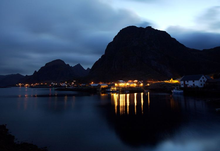 Scenic view of illuminated bay against sky