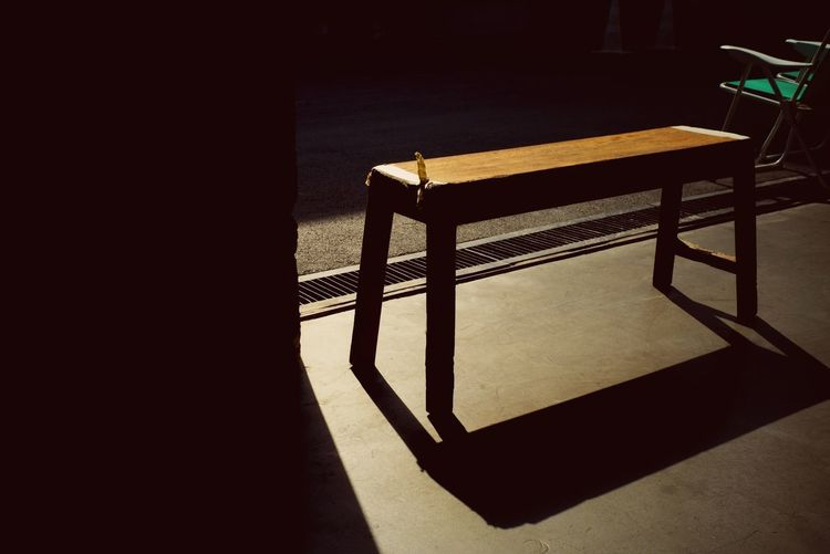 Empty wooden bench stands on the cement floor with shadow from the light of sunset processed in vintage tone. Classical style furniture at the gate of house Loneliness And Sadness Abstract Empty Bench Silhouette Shadow Seat Table Sunlight Indoors  No People Chair High Angle View Architecture Flooring Nature Absence Day Still Life Empty Furniture Building