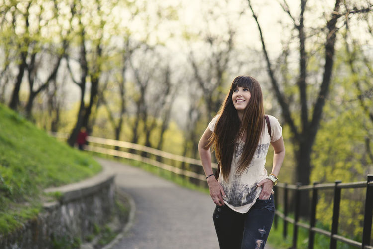 beautiful young woman walking outside in the girl with long brown hair smiling Beautiful Woman Casual Clothing Day Focus On Foreground Hair Hairstyle Leisure Activity Lifestyles Long Hair Looking At Camera One Person Outdoors Plant Portrait Railing Real People Standing Three Quarter Length Tree Young Adult Young Women