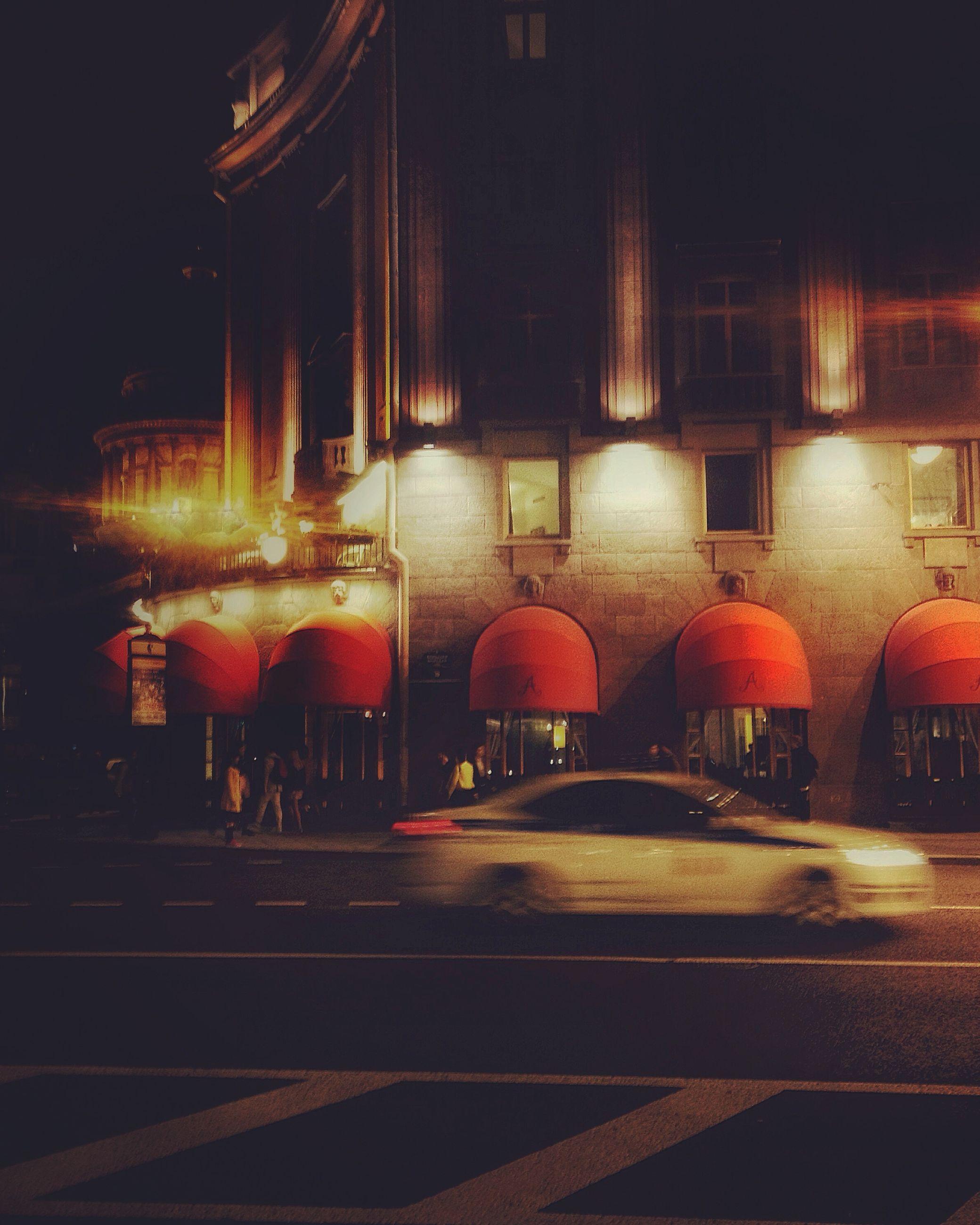 illuminated, night, building exterior, architecture, built structure, street, lighting equipment, city, street light, transportation, red, road, outdoors, light - natural phenomenon, no people, sidewalk, incidental people, city life, car, city street